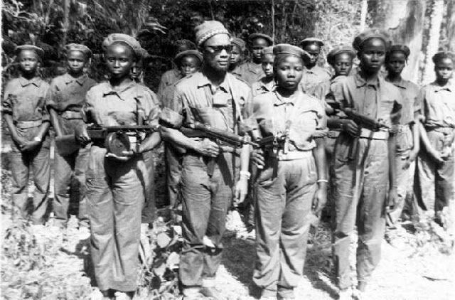 Cabral wearing sun glasses with a weapon in his hands surrounded by feminine troops of his army