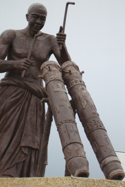 Statue representing an initiated man speaking the drum's language and delivering a message.