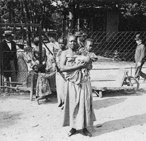 A Black woman with her child enclosed in railings at a human zoo. Behind her, people are passing by and staring at her.